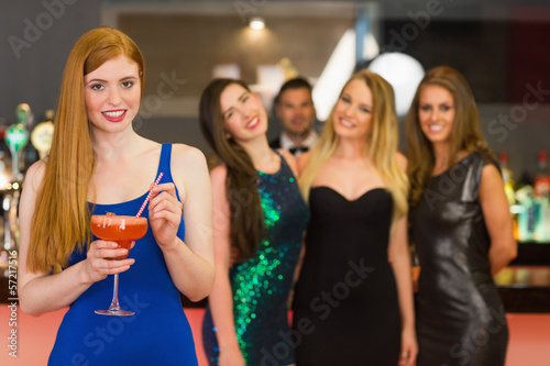 Attractive woman holding cocktail standing in front of her frien