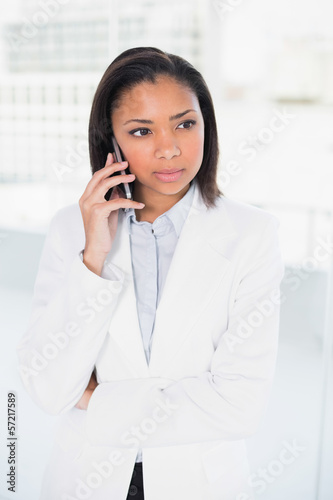Thoughtful young dark haired businesswoman making a phone call