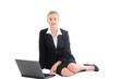 Attractive blonde businesswoman sitting on floor using her noteb
