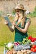 Young female farmer checking her tablet at her stall