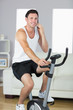 Content sporty man exercising on bike and phoning