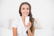 Smiling pretty brunette holding glass of milk