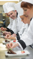 Team of chefs in a row garnishing dessert plates one smiling at