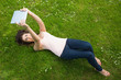 Happy young woman lying on a lawn using her tablet