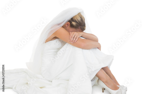 Unhappy blonde bride sitting on floor
