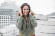 Smiling gorgeous brunette in winter fashion listening to music