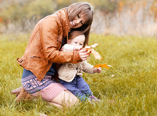 Happy mother holding her little child on the forest field