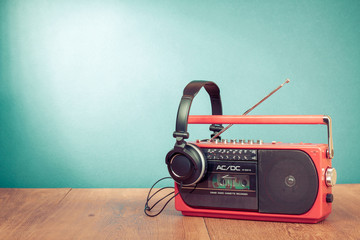 Retro cassette player and phones in front mint green background