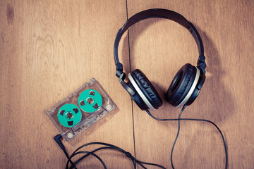 Retro compact cassette with rolls and headphones on wood