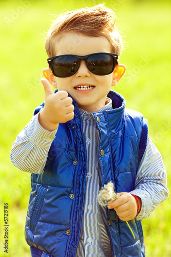 Stylish laughing baby boy with ginger (red) hair in sunglasses