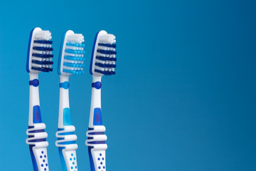 Three shiny new toohbrush on blue background with copy space