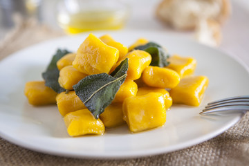 delicious pumpkin gnocchi with sage leaves and olive oil, vegan