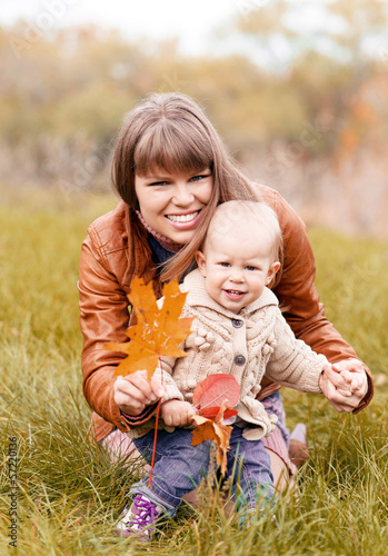 Happy smiling woman holding her cute blond child outdoors