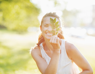 Smiling young woman showing branch with leaves