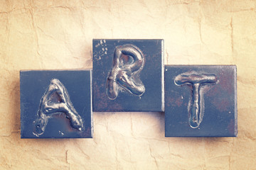 "The word ""ART"" made from metal letters on an old vintage paper b"
