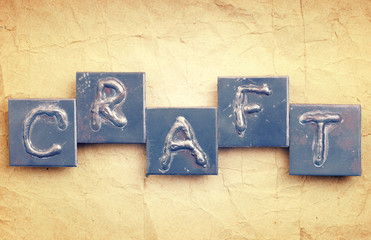 "The word ""CRAFT"" made from metal letters on an old vintage paper"