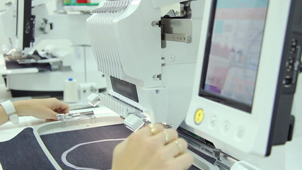 Woman working on computerized machine embroidery