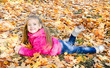 Autumn portrait of cute little girl lying in maple leaves