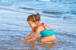girl in a blue bathing suit playing in the water