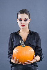 beautiful girl with pumpkin in the studio isolated on gray backg