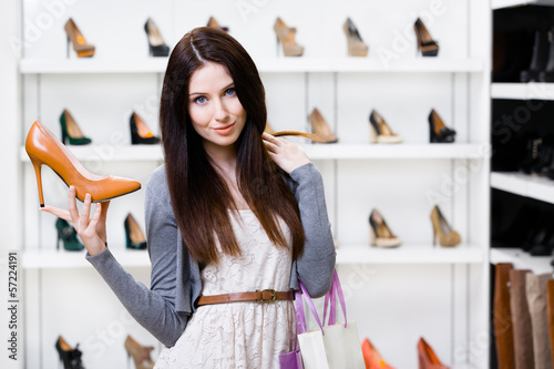 Half-length portrait of woman keeping brown leather stylish pump