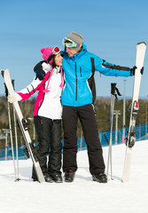 Full-length portrait of two embracing skiers with skis in hands