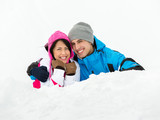 Man and girl lying in snow embrace each other
