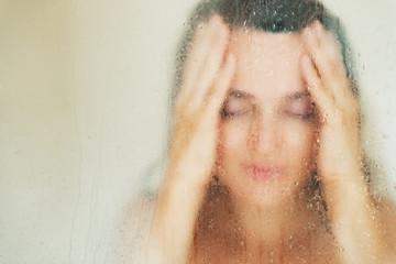 Young woman behind weeping glass shower door