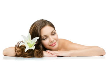Relaxed girl with lily in hair lies with eyes closed, isolated