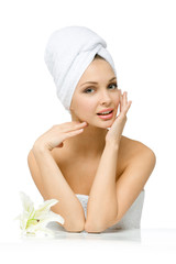 Naked girl with towel on head touches her face