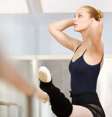 Female ballet dancer stretches herself near barre and mirrors