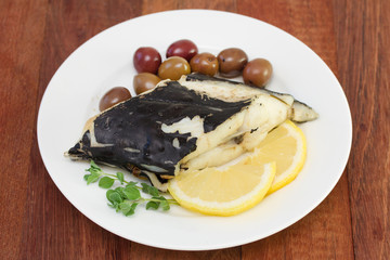 fish with olives and lemon on white plate