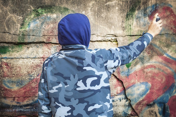 Boy with color spray can near the wall