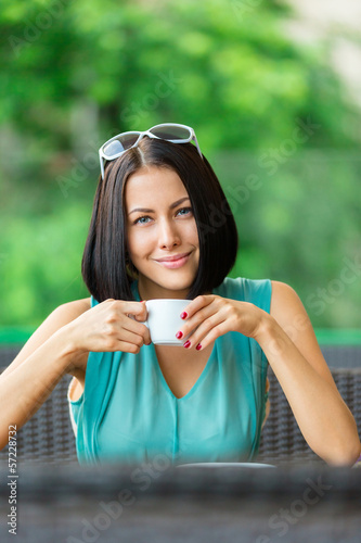 Girl wearing blue dress and sunglasses drinks tea