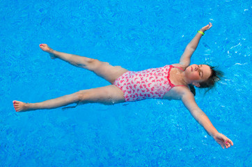 Child girl laying on the swimming pool water surface