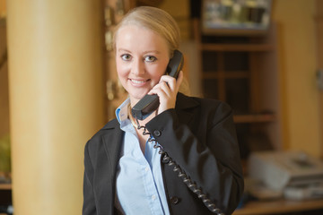 Beautiful blond woman answering a telephone