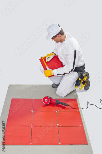 Worker Cuts red Ceramic Tile with Machine Tiling