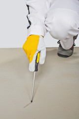 worker with sharp tool checking cement floor