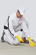 Construction worker with sponge cleans cement substrate