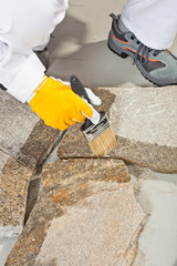 Construction worker with brush lays primer grout of stones joint