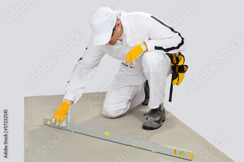Construction worker checks levels of cement-base