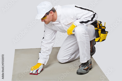 Construction worker with sand paper cleans cement substrate