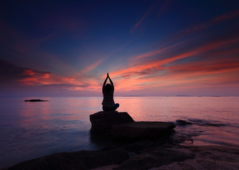 Silhouette yoga girl by the beach  sunset