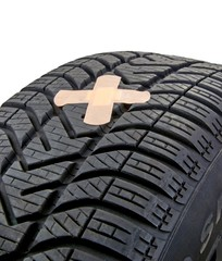 A damaged car tyre with puncture and first aid plaster