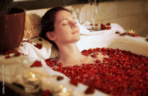 canvas print picture Woman relaxing in bathtub with rose blossoms