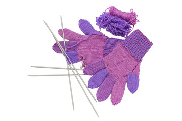 Unfinished knitted gloves with needles isolated on white