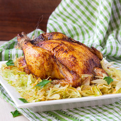 Roasted whole chicken with golden crust and garnish of cabbage
