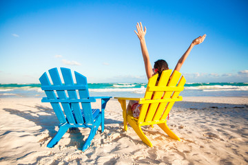 Young woman in beach chair raised her hands up on white beach