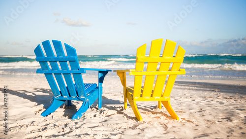 Two wooden chairs: yellow and blue on a white sandy beach,