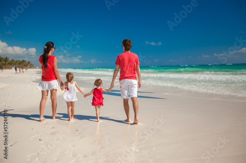 Back view of family of four on beach vacation